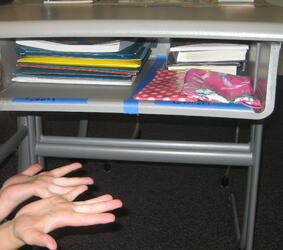 After Executive Function coaching, a student proudly displays her newly organized desk.
