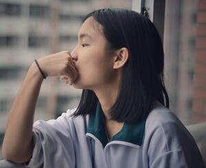 Stressed and anxious high school student looking out a window