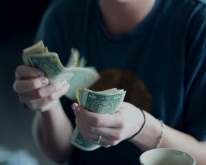 Woman counting the money she has wasted with her ineffective habits
